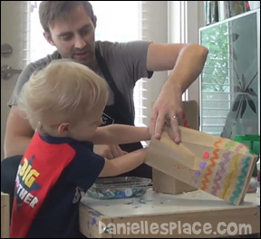 Preschool child using fine motor skills to stuff a bag to make a craft with his father.