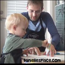Two-year-old Logan makes a spiral snake with his dad.