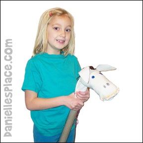 Danielle holding a stick horse she made